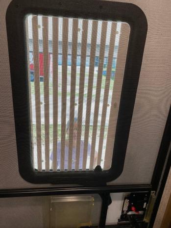 Entry door window with operable shade.